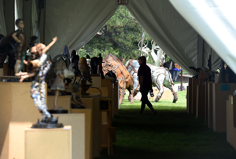 Michele Van Wechel, a long-time Sculpture in the Park volunteer, gets a peek inside one of the tents Friday, Aug. 11, 2017, before the show starts.   (Photo by Jenny Sparks/Loveland Reporter-Herald)