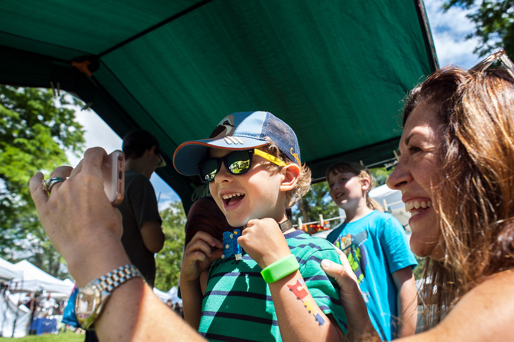 . Zakary Cavanagh, 5, and his mother Marlene Cavanagh of Loveland react as Zakary tries on a Lego bow tie at the Son and Pop Bow Tie Shop during Art in the Park in North Lake Park on Sunday, August 13.