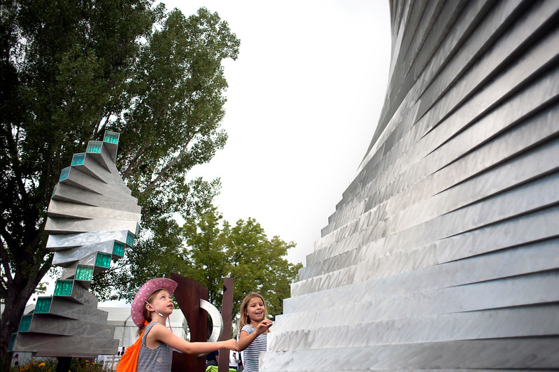 Friends Kinzie Graf, 8, and Keilana Surrett, 8, twist an aluminum and glass sculpture by artist Brian Schader of Fountain Hills, Ariz. on Saturday, August 12, during the Sculpture in the Park Show and Sale at Benson Sculpture Garden.