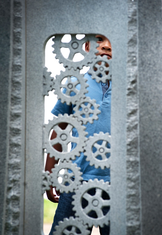 """. Kwayedza Tafura, 4, of Longmont takes a look at a granite sculpture called \""""Ancient Gears\"""" by Scott Luken of Yankton, S. Dakota on Saturday, August 12, during the Sculpture in the Park Show and Sale at Benson Sculpture Garden. Tafura was at the show with his father Stalin Tafura who is also a sculptor."""