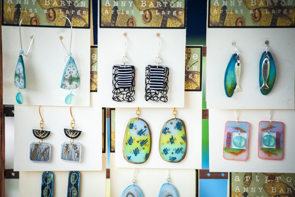 . Loveland artist Anny Barton displays her jewelry during Art in the Park in North Lake Park on Sunday, August 13. Barton uses the Shrinky Dinks paper, made popular in the 70s and 80s, to print her designs.