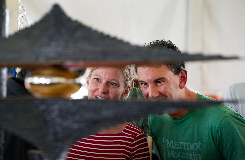 """. Katie and Corey Charboneau of Loveland talk with their friend and artist Ted Schall, also of Loveland on Saturday, August 12 during the Sculpture in the Park Show and Sale in Benson Sculpture Garden. Schall\'s sculpture entitled \""""Desert Mirage,\"""" through which the couple is visible, was inspired by a real mirage of a mountain and dry lake bed that the artist saw while traveling through the Nevada desert."""