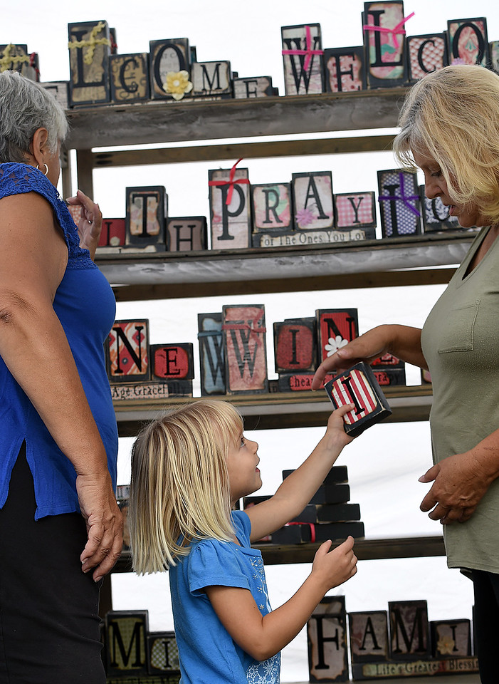 Mackenzie Collins, 4, hands a letter to Becky Mackin, right, as they and Lori Leckner, left, set up Leckner's Plan B Designs Co booth Friday, Aug. 11, 2017, at Art in the Park in Loveland.   (Photo by Jenny Sparks/Loveland Reporter-Herald)