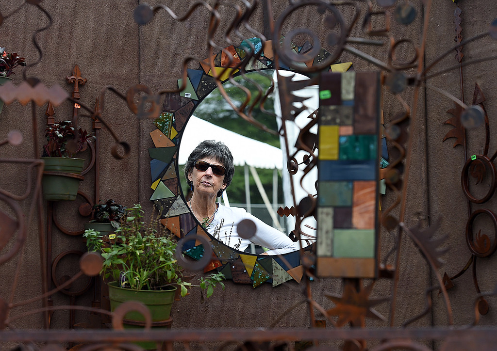 . Paula Weiman of Loveland is reflected in a mirror Friday, Aug. 11, 2017, while checking out artist Nicole Brin\'s booth at the Fine Art & Wine Invitational in Loveland.   (Photo by Jenny Sparks/Loveland Reporter-Herald)