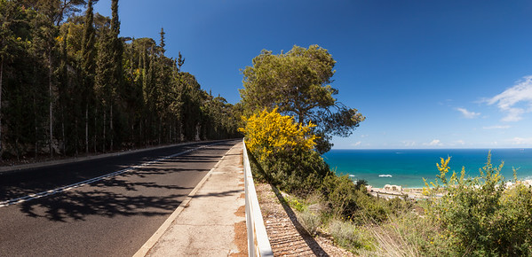 Panoramic view of mountain road with trees, cloudy sky and Medditerian sea on the background