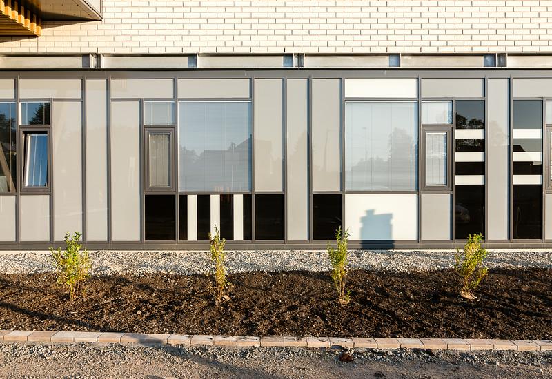 Østfasade - glassfelt på poliklinikk. Grafikk på glass med motiv fra Hurtigrutens skorsteiner. Kunstner: Lise Stang Lund.