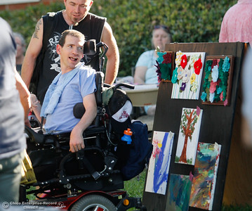 Ian Winchester looks back and smiles at the artwork hanging during the annual Art on the Green Wednesday September 14, 2016 at the Joe McGie Center in Chico, Calif. The art show featured work by clients of the Work Training Center, live music and food. All proceeds from the art sale benefited the Joe McGie Center, a division of the Work Training Center.Wednesday September 14, 2016 in Chico, Calif. (Emily Bertolino -- Enterprise-Record)