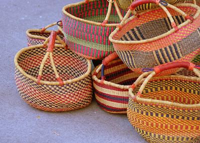 Multi-colored baskets on the sidewalk.