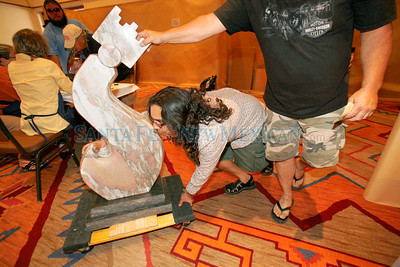 Upton Ethelbah 3rd, left, and Rick Weza, from Seatle, push a marble sculpture by artist Upton Ethlbah Jr. after checking it into Indian Market at the Santa Fe Community Convention Center on Aug. 18, 2010.             Luis Sanchez Saturno/ The New Mexican.