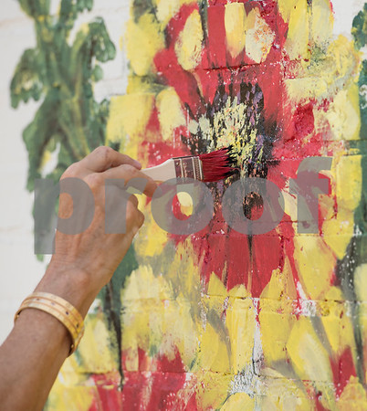 """Becky Martin of Tyler paints these flowers as one part of a large mural being painted by a group of Tyler area artists on the back side of the ETX Brewing Co. building in downtown Tyler on Friday June 15, 2018. When finished, the mural will depict native flowers painted by 14 different artists along with the phrase """"Be Happy.""""   (Sarah A. Miller/Tyler Morning Telegraph)"""