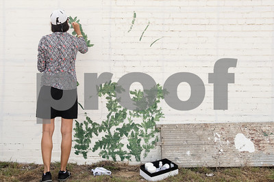 """Becky Martin of Tyler paints flowers as one part of a large mural being painted by a group of Tyler area artists on the back side of the ETX Brewing Co. building in downtown Tyler on Friday June 15, 2018. When finished, the mural will depict native flowers painted by 14 different artists along with the phrase """"Be Happy.""""   (Sarah A. Miller/Tyler Morning Telegraph)"""