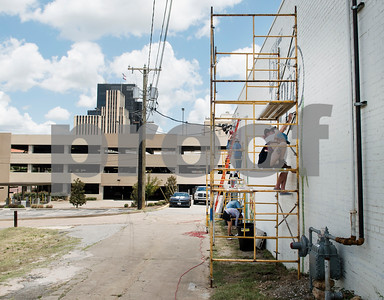 """A group of Tyler area artists begin painting the back side of the ETX Brewing Co. building in downtown Tyler on Friday June 15, 2018. When finished, the mural will depict native flowers painted by 14 different artists along with the phrase """"Be Happy.""""   (Sarah A. Miller/Tyler Morning Telegraph)"""