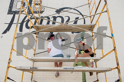 """Artists Lindsay Boone and Britt Belvail sit on a scaffolding as they begin painting a 800-square-foot mural on the back side of the ETX Brewing Co. building in downtown Tyler on Friday June 15, 2018. When finished, the mural will depict native flowers painted by 14 different artists along with the phrase """"Be Happy.""""   (Sarah A. Miller/Tyler Morning Telegraph)"""