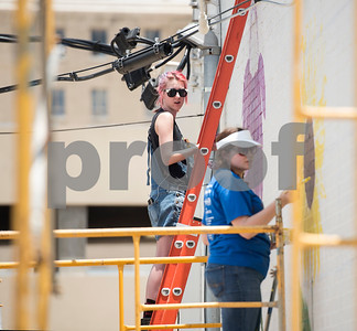 """Madeline Travis of Flint and Mikayla Willis of Bullard paint part of a large mural being painted by a group of Tyler area artists on the back side of the ETX Brewing Co. building in downtown Tyler on Friday June 15, 2018. When finished, the mural will depict native flowers painted by 14 different artists along with the phrase """"Be Happy.""""   (Sarah A. Miller/Tyler Morning Telegraph)"""