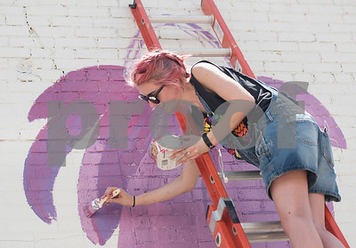 """Madeline Travis of Flint paints a purple flower as one part of a large mural being painted by a group of Tyler area artists on the back side of the ETX Brewing Co. building in downtown Tyler on Friday June 15, 2018. When finished, the mural will depict native flowers painted by 14 different artists along with the phrase """"Be Happy.""""   (Sarah A. Miller/Tyler Morning Telegraph)"""