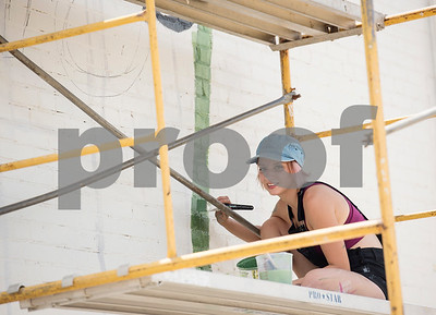 """Britt Belvail sits on a scaffolding to paint a 800-square-foot mural on the back side of the ETX Brewing Co. building in downtown Tyler on Friday June 15, 2018. When finished, the mural will depict native flowers painted by 14 different artists along with the phrase """"Be Happy.""""   (Sarah A. Miller/Tyler Morning Telegraph)"""