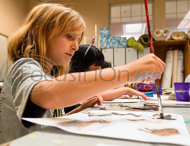 Eight-year-old Sarah Weissmann paints glue over her Picasso-inspired collage made out of old magazine clippings during Petite Picasso camp Tuesday in the Jenkins Building at Tyler Junior College.   (Cara Campbell/Tyler Morning Telegraph)