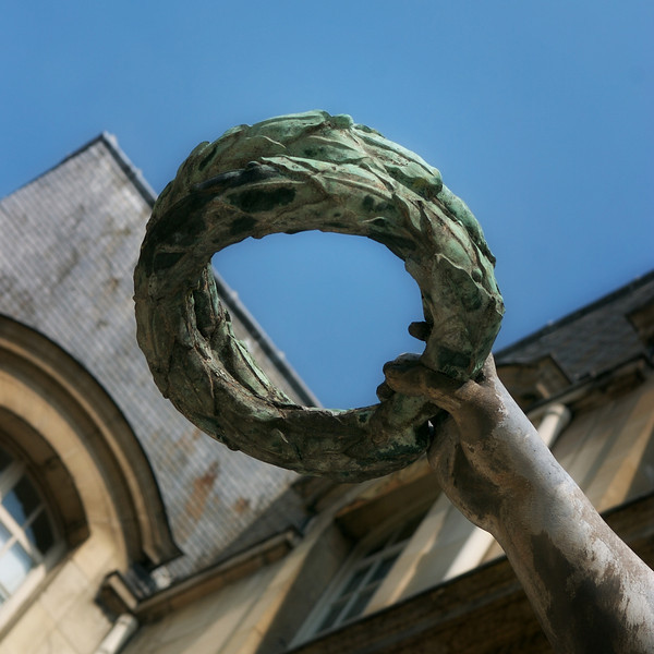 """Q"" A laurel wreath held up by a statue"