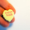 Sweet Thing on Yellow Candy Heart in a hand.