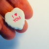 I Heart You, I love You White Candy Heart in Hand with White & Blue Background