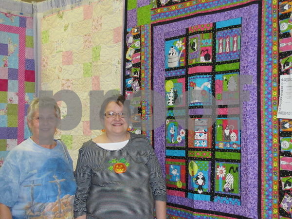 Kris Olson of Carroll and Marion Dencklau of Thor pose among the many hanging quilts on display.