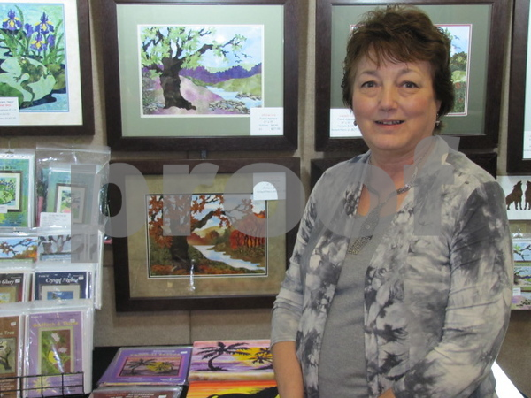 Doris Deutmeyer of Dyersville, IA stands with some of her many creations.  Deutmeyer designs fabric landscapes and patterns, and gives lectures and workshops on her craft.