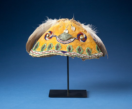 The cap dated from the last quarter of the 19th century, ca. 1870.  It is made of typical Apache-cured deer hide which was ochered yellow.  It has typical restrained Apache beadwork, and German silver attachments.  The two feathers are exact replicas of the original eagle feathers.