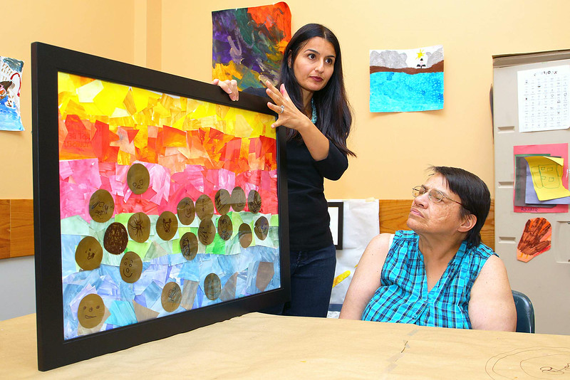 Artist Sheila Freeman listens as Art Therapist Krista Bebezas talks about this piece of art by many students in her class that will be featured in an upcoming art show put on by The Arc of Opportunity in Fitchburg.  SENTINEL & ENTERPRISE/JOHN LOVE