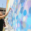 Clients, their family members and staff of the Arc of Opportunity participated in helping paint Caleb Neelon's mural on the side of the Arc of Opportunity building. Helping out is Esther Serrano the Arc Human Resource Assistant. SENTINEL & ENTERPRISE/JOHN LOVE