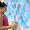 Clients, their family members and staff of the Arc of Opportunity participated in helping paint Caleb Neelon's mural on the side of the Arc of Opportunity building. Helping out is Abrianna Fusco, 12. SENTINEL & ENTERPRISE/JOHN LOVE