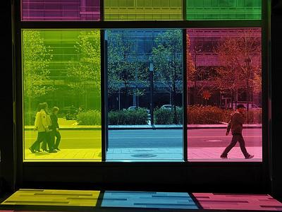"""Walking in the colours: picture of peoples walking on the sidewalk outside the """"Palais des congrès"""" in Montréal. / Photo de rue prise de l'interieure du Palais des congres a Montreal."""