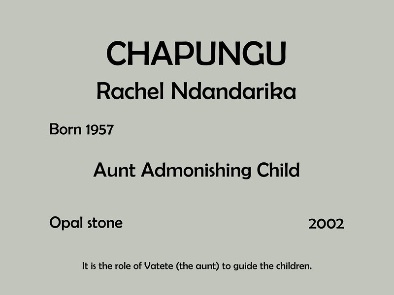 Aunt Admonishing Child IM00<br /> Rachel Ndandarika (Born 1957)<br /> Opal Stone; 2002<br /> <br /> This image is a recreation of the interpretive sign for this sculpture.  The actual sign was so badly worn and so dirty that its readability was compromized.<br /> <br /> Chapungu Exhibit<br /> Powell Gardens, Missouri<br /> Taken October 1, 2008; re-edited 2017-18