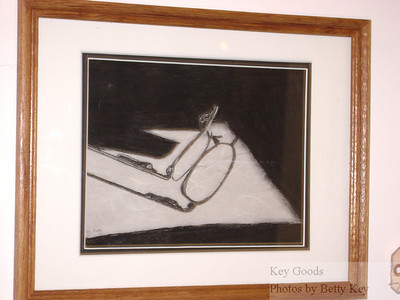 """See the Light"" - photo taken at the UMB Art Week Show. This is a pencil and charcoal drawing that I did from a photograph that I took one day at work when the sun was streaming in from the window above - and this patch of bright light was forming the shadow of my reading glasses on my cubicle desk. The drawing is on a paper that is printed to look like a handmade paper that I thought simulated the speckle of my desk."