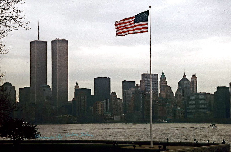NYC_New_York_Lower_Manhattan_from_Liberty_Island_with_Flag_b