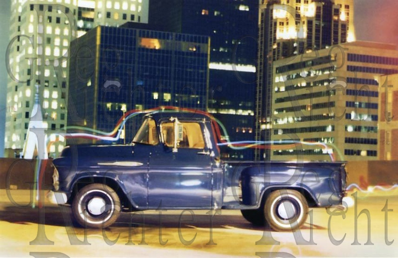 `1957 Chevrolet pickup in city lights