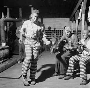 """In the convict camp in Greene County, Georgia"", 1941. Blues musician Buddy Moss is playing guitar; other men unidentified. Man at left dancing. FSA photo by Jack Delano. Via Library of Congress site at [1]. http://www.loc.gov/pictures/resource/fsa.8c29075/"