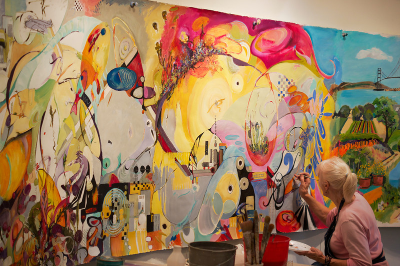 Artist painting her portion of a large canvas for an upcoming fundraiser.  Marin Museum of Contemporary Art  ref: 9516c7d6-1b43-4921-a83f-96cf13d527fb