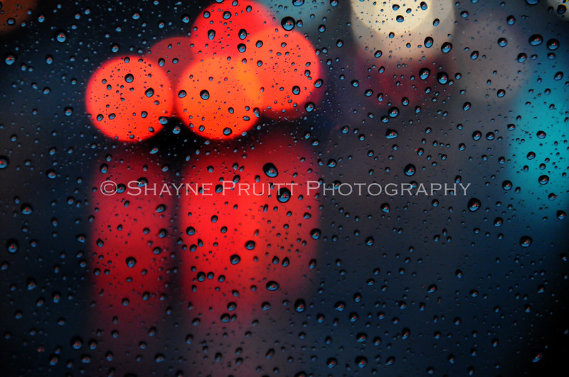 Traffic and brake lights at dusk on a stormy evening shot through my car window. Focus was on the water droplets.