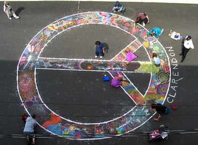 Recommended Group Project for the Public: CHALKPEACE Symbol Take some rope and a big piece of sidewalk chalk Tie the chalk and have someone hold the end of the rope  tight to a center point. Pulling the rope taut, draw one  large circle, then repeat a smaller circle 2-3 feet smaller.  Get someone who CAN draw straight lines create the  inner forms with a long 2 x 4 or a surveyor's chalk line. Make these lines BOLD with chalk.  Scatter loose chalk inside the lines and watch it happen! photo: John Aaron