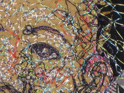 Detail of face. I use lots of colors and lots of different thread types. None of this thread is functional and so it can be rayon or cotton or silk or trilobal polyester depending upon its color
