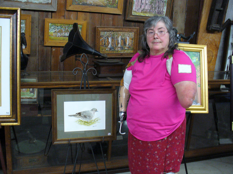 Cheryl Hoyt, stands with her painting during the reception before the buyer picks it up the next day.