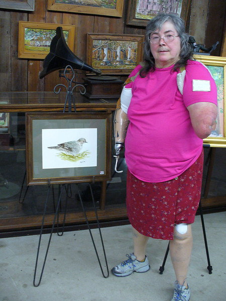 Jude's mother, Cheryl Hoyt, stands with her painting at the Rural Life Museum.