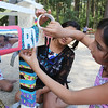 Ria Vasishtha, 10, of Lexington, and her aunt, Geetika Kaw of Bedford, decorate a temporary structure for Art in the Park day at Springs Brook Park in Bedford. (SUN/Julia Malakie)