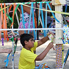 Vivek Kaw, 8, of Bedford, and his cousin Ria Vasishtha, 10, of Lexington, decorate a temporary structure for Art in the Park day at Springs Brook Park in Bedford. (SUN/Julia Malakie)