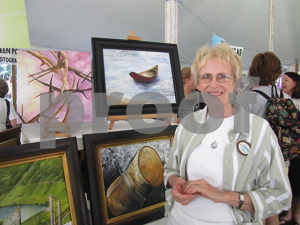 Artist Mary Jo Hinds with her paintings at the Blanden Arts Fest.