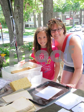 Hannah Kippes, granddaughter of artist Evy Somsen, with Sue Gottsch making handmade paper at Somsen's booth.