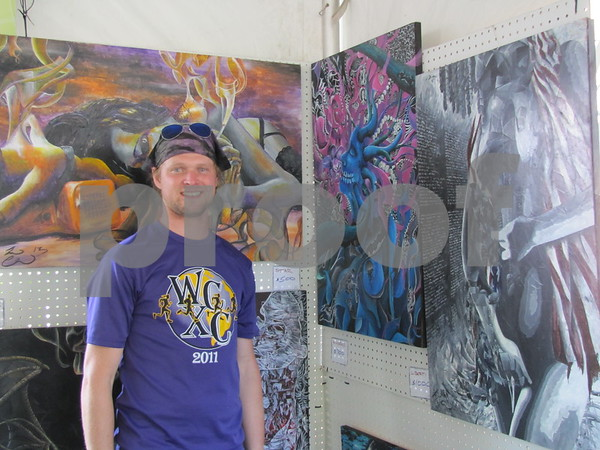 Artist Leo Clark from Chicago stands with his paintings for sale at the Blanden Arts Fest.