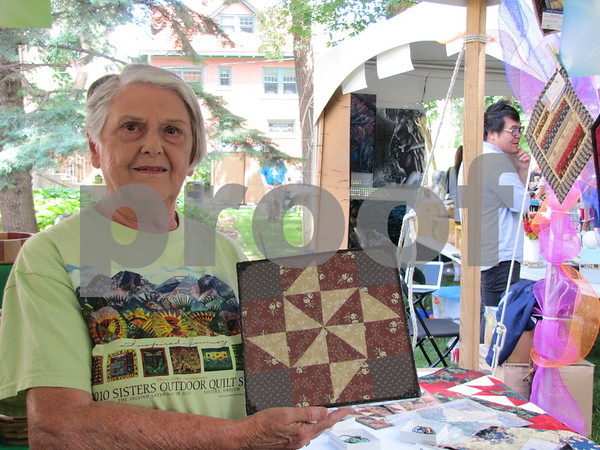 Artist Betty Heiden holds one of her unique framed quilt pieces.