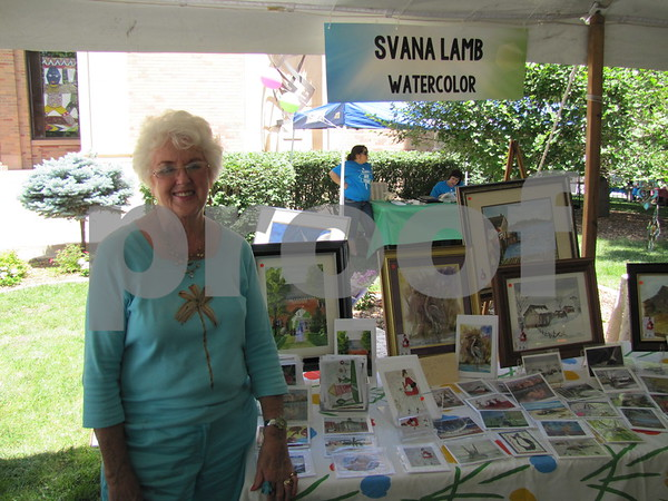 Artist Svana Lamb with her watercolor paintings. Some of  Lamb's pieces can be found in the Blanden gift shop.