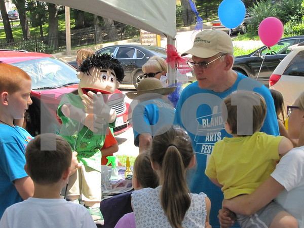 Doug Brightman, committee member of the Blanden Arts Fest, shows the children how to operate his puppet Kenny.